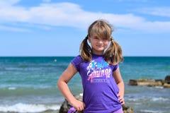 Niña que presenta en la playa Fotografía de archivo