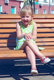 Niña que ríe mientras que se sienta en banco en parque de la ciudad Emociones positivas del ` s de los niños Fotografía de archivo libre de regalías