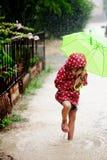 Niña que recorre en la lluvia Imagen de archivo libre de regalías