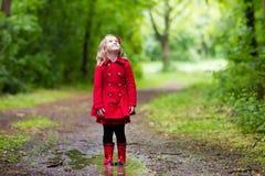 Niña que recorre en la lluvia Foto de archivo libre de regalías
