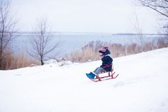 Niña que resbala abajo de la colina de la nieve con su padre fotos de archivo