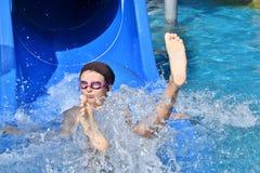 Niña que resbala en el tobogán acuático durante vacaciones en sommer Fotografía de archivo libre de regalías