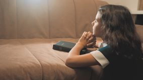 Niña que ruega en la noche Rogación de la mano de la niña la Sagrada Biblia de la niña ruega forma de vida con la biblia en ella almacen de metraje de vídeo