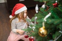Niña que se arrodilla en el piso que adorna el árbol de navidad Fotografía de archivo