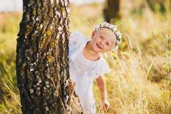 Niña que se coloca detrás de un árbol en el parque al aire libre, jugando escondite, un vestido blanco hermoso Imagenes de archivo