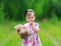 Niña que se coloca en la hierba que sostiene el oso de peluche grande fotografía de archivo libre de regalías