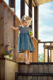 Niña que se coloca en las escaleras de madera de una casa de campo Fotos de archivo