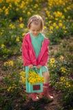 Niña que se coloca en prado del amarillo de la primavera Flores del verano de la cosecha del niño Niños en país imágenes de archivo libres de regalías