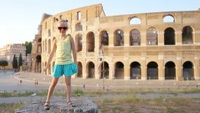 Niña que se divierte delante de Colosseum en Roma, Italia Niñez del gasto del niño en Europa metrajes