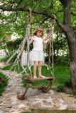 Niña que se divierte en un oscilación al aire libre Niño que juega, patio del jardín Fotografía de archivo libre de regalías