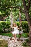 Niña que se divierte en un oscilación al aire libre Niño que juega, patio del jardín Imagenes de archivo