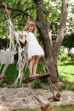 Niña que se divierte en un oscilación al aire libre Niño que juega, patio del jardín Fotos de archivo libres de regalías