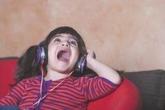 Niña que se divierte que escucha la música Imagen de archivo