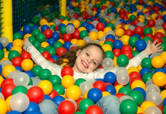Niña que se divierte que juega con las bolas plásticas coloridas Fotografía de archivo