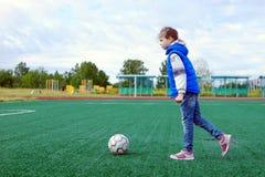 Niña que se prepara para golpear con el pie en la bola en un campo de fútbol con el césped artificial al aire libre imagenes de archivo