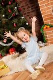 Niña que se sienta cerca del árbol de navidad Fotos de archivo libres de regalías