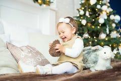 Niña que se sienta con una liebre en el fondo de árboles Feliz Navidad Foto de archivo libre de regalías
