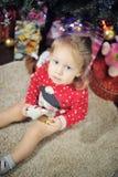 Niña que se sienta contra la decoración de la Navidad Foto de archivo
