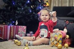 Niña que se sienta contra la decoración de la Navidad Imágenes de archivo libres de regalías