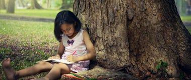 Niña que se sienta debajo de un árbol grande y que escribe un libro Foto de archivo libre de regalías
