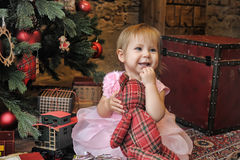 Niña que se sienta debajo del árbol de navidad Fotos de archivo