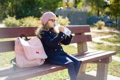Niña que se sienta en banco con la mochila de la escuela, agua potable de la botella Parque de la ciudad del fondo Fotos de archivo libres de regalías