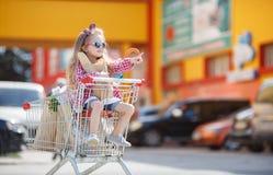 Niña que se sienta en carretilla de las compras Imagen de archivo libre de regalías