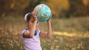Niña que se sienta en el bosque del otoño que sostiene un globo viaje de la geografía de la niña pequeño niño feliz, bebé metrajes