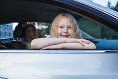 Niña que se sienta en el coche cerca de la ventana Foto de archivo libre de regalías