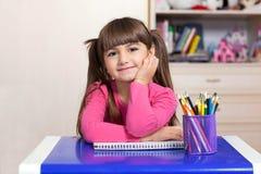 Niña que se sienta en el cuarto de niños en la tabla con color Imagen de archivo