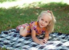 Niña que se sienta en el parque Foto de archivo libre de regalías
