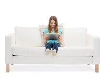 Niña que se sienta en el sofá con el comuter de la PC de la tableta Imagenes de archivo