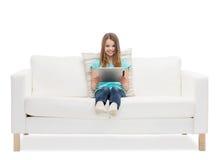 Niña que se sienta en el sofá con el comuter de la PC de la tableta Fotografía de archivo
