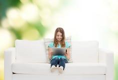 Niña que se sienta en el sofá con PC de la tableta Imagenes de archivo