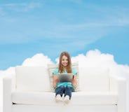 Niña que se sienta en el sofá con PC de la tableta Imagen de archivo