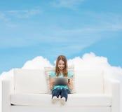 Niña que se sienta en el sofá con PC de la tableta Fotografía de archivo libre de regalías