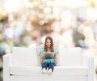 Niña que se sienta en el sofá con PC de la tableta Imagen de archivo libre de regalías