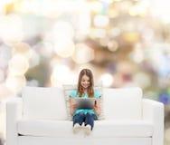 Niña que se sienta en el sofá con PC de la tableta Fotografía de archivo
