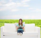 Niña que se sienta en el sofá con PC de la tableta Foto de archivo libre de regalías