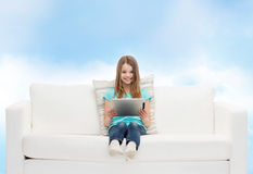 Niña que se sienta en el sofá con PC de la tableta Foto de archivo