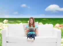 Niña que se sienta en el sofá con PC de la tableta Fotos de archivo libres de regalías