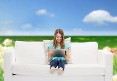 Niña que se sienta en el sofá con PC de la tableta Imágenes de archivo libres de regalías