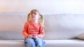 Niña que se sienta en el sofá y que llora, madre que grita en el niño para el mún comportamiento n metrajes