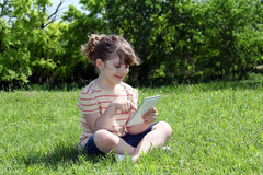 Niña que se sienta en hierba y juego con la tableta Imagen de archivo
