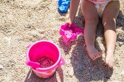 Niña que se sienta en la arena y que juega con los juguetes plásticos Fotografía de archivo
