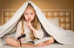 Niña que se sienta en la cama y que lee un libro Imágenes de archivo libres de regalías