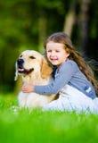 Niña que se sienta en la hierba con Labrador fotografía de archivo