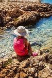 Niña que se sienta en la orilla rocosa del mar Fotografía de archivo libre de regalías