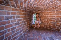 Niña que se sienta en la pared de la fortaleza Imágenes de archivo libres de regalías