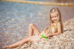 Niña que se sienta en la playa cerca del mar Imagen de archivo